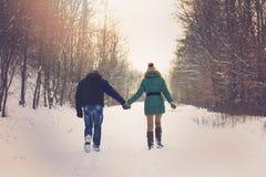 在浪漫冬天步行的夫妇 免版税库存图片