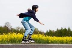 直排轮式溜冰鞋的女孩 免版税图库摄影