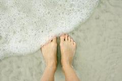 妇女的脚在海滩的海洋 免版税图库摄影