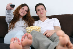 Молодые пары смотря ТВ и есть попкорн Стоковое фото RF