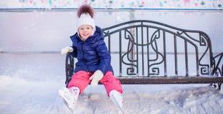 小女孩坐一条长凳在滑冰场 库存图片