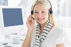 有耳机的微笑的偶然少妇在办公室 免版税库存照片