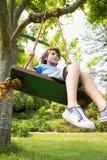 低角度观点的摇摆的一个逗人喜爱的小男孩 免版税图库摄影
