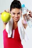 年轻微笑的体育妇女用苹果和瓶水 免版税图库摄影