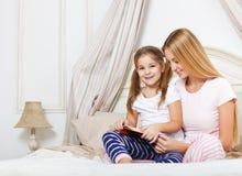 照顾读书床时间故事书给她的女儿 库存照片