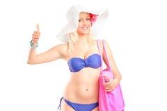 给赞许的比基尼泳装的可爱的白肤金发的妇女 免版税库存照片