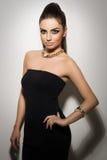 Мода. Красивая женщина представляя в черном платье Стоковые Изображения