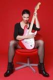 Γυναίκα στο κόκκινο υπόβαθρο με την ηλεκτρική κιθάρα Στοκ Φωτογραφίες