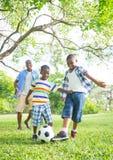 踢橄榄球的男孩在公园 库存照片