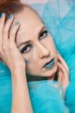 Κομψή όμορφη γυναίκα σε μια μπλε χοντροσκαλίδρα γάζας Στοκ Εικόνες