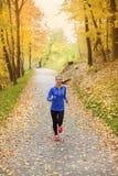 在秋天自然的活跃和运动的妇女赛跑者 免版税库存图片