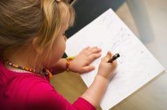 与笔的小女孩图画 免版税图库摄影