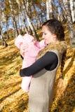 拥抱和笑在自然秋天的愉快的妈妈和儿童女孩。快乐的童年和家庭的概念。 免版税库存图片