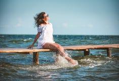 一件白色礼服的妇女在海滩 库存照片