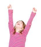 欢呼与胳膊的愉快的女孩被举 免版税库存图片
