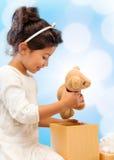 有礼物盒和玩具熊的愉快的儿童女孩 免版税库存图片