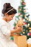有礼物盒和玩具熊的愉快的儿童女孩 库存照片