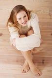 美丽的无忧无虑的年轻偶然妇女坐地板。 免版税库存照片