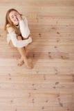 美丽的无忧无虑的年轻偶然妇女坐地板。 免版税图库摄影
