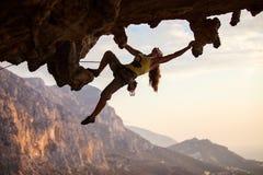 Альпинист утеса на заходе солнца Стоковые Фото
