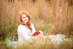 Красная с волосами девушка в усмехаться поля Стоковые Фото