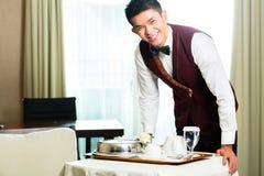Ασιατικά κινεζικά εξυπηρετώντας τρόφιμα σερβιτόρων υπηρεσιών δωματίων στο ξενοδοχείο Στοκ εικόνα με δικαίωμα ελεύθερης χρήσης