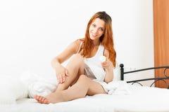 Χαμογελώντας γυναίκα που φροντίζει για τα πόδια Στοκ εικόνα με δικαίωμα ελεύθερης χρήσης
