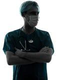 篡改外科医生与面罩剪影的人画象 库存图片