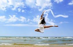 跳跃在海滩的美丽的女孩 库存照片