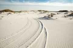 在海滩沙丘的轮胎轨道在黄昏 免版税库存照片