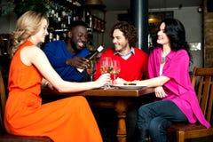 享受晚餐的四个朋友在餐馆 免版税库存照片