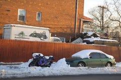 在雪下的汽车和铃木摩托车 免版税库存照片