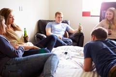 喝酒精的小组少年在卧室 免版税库存图片