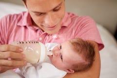 给小女儿瓶牛奶的父亲 免版税库存照片
