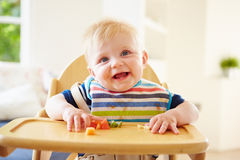 吃在高脚椅子的男婴果子 免版税库存图片
