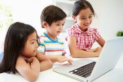 在家使用膝上型计算机的三个亚裔孩子 免版税图库摄影