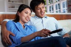 亚洲夫妇坐一起看电视的沙发 免版税库存照片