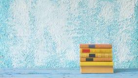 堆在蓝色墙壁上的书 免版税库存照片