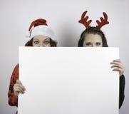 拿着空白的标志的两名俏丽的妇女 免版税库存图片