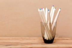 上色在玻璃的铅笔在木背景 免版税库存图片