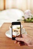 拍咖啡的照片智能手机 免版税库存图片