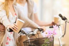 拿着咖啡和骑自行车的夫妇 免版税库存照片