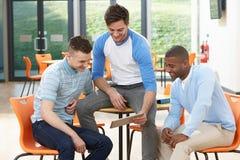 看数字式片剂的三名男学生在教室 免版税图库摄影