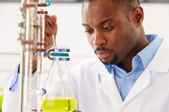 学习在烧瓶的科学家液体 库存图片