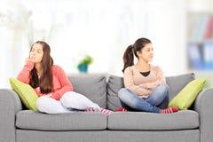 两个恼怒的十几岁的女孩坐沙发,在家, 免版税库存照片