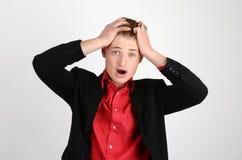 Молодой бизнесмен держа его голову хмурясь с беспокойством кричащий. Стоковая Фотография