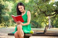 有暴牙的微笑阅读书的美丽的少妇在公园 免版税库存图片