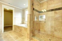 有木盆和玻璃门阵雨的舒适卫生间 免版税图库摄影