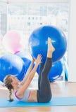 拿着在腿之间的运动的妇女锻炼球在健身演播室 免版税库存照片