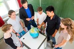 Студенты учителя уча уроки землеведения в школе Стоковое фото RF